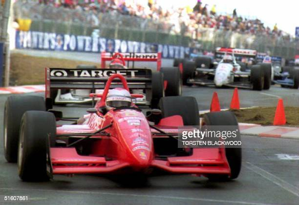 Race driver Michael Andretti leads second-place Brazilian driver Emerson Fittipaldi and third-place Mario Andretti, the leader's father, through the...