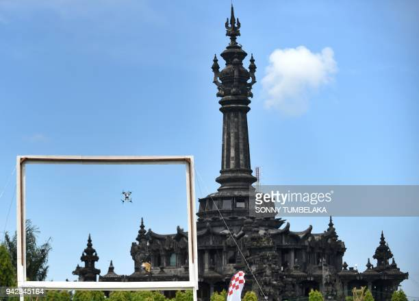 A race drone flies through a gate in front of the Bajra Sandhi monument during the FAI Drone Racing World Cup event in Denpasar on Indonesia's resort...
