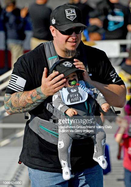 A race fan covers a babies ears during the first round of eliminations in Pomona on Sunday November 11 2018 at the 54th annual NHRA Finals at Auto...