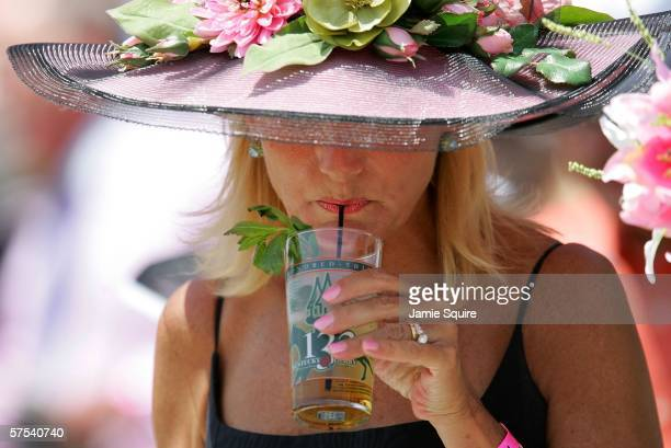 Race fan Mary Woolsey watches the 6th race the Third Running of the Alysheba while sipping a Mint Julep on Kentucky Oaks day on May 5 2006 at...
