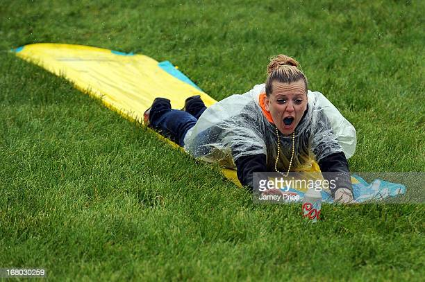 A race fan slides down a Slip N Slide in the infield while it rains prior to the 139th running of the Kentucky Derby at Churchill Downs on May 4 2013...