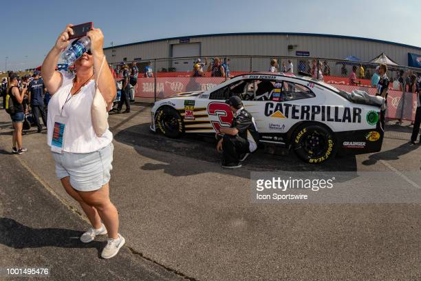 A race fan takes a selfie with the car of Ryan Newman driver of the Caterpillar Chevrolet in the background before the Monster Energy NASCAR Cup...