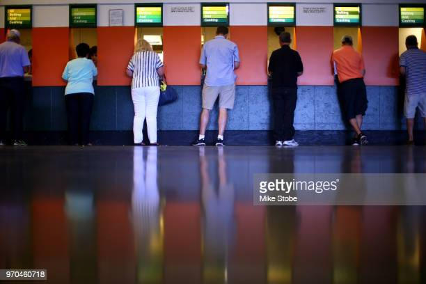 Race fans place bets at the wagering window prior to the 150th running of the Belmont Stakes at Belmont Park on June 9 2018 in Elmont New York