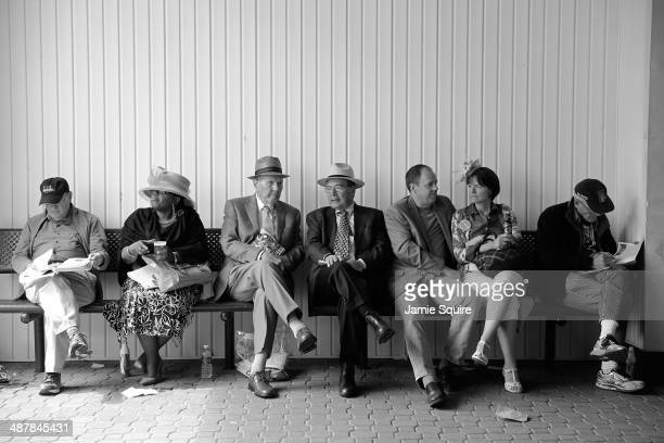 Race fans sit while wearing festive hats prior to the 140th running of the Kentucky Oaks at Churchill Downs on May 2 2014 in Louisville Kentucky