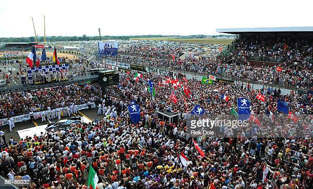 Race fans swarm onto the Le Mans track to enjoy the victory podium celebrations during the 77th running of the Le Mans 24 Hour race at the Circuit...