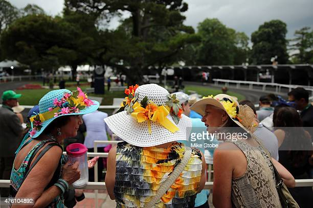 Race fans wearing fancy hats are seen in the paddock during the 147th running of the Belmont Stakes at Belmont Park on June 6 2015 in Elmont New York