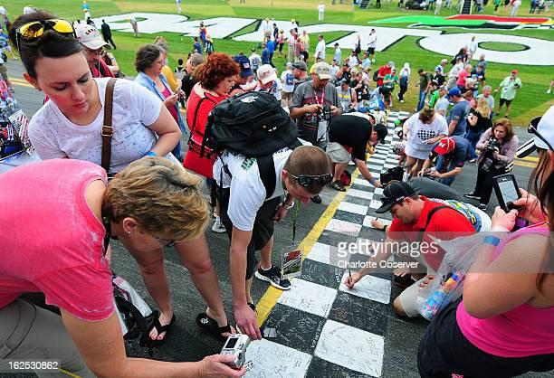 Race fans write messages and sign the start/finish line at Daytona International Speedway in Daytona Beach Florida Sunday February 24 2013