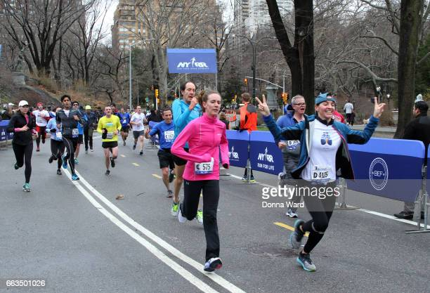 Race finishers cross the finish line during Boomer's Cystic Fibrosis 'Run To Breathe' Charity Event at Central Park Bandshell on April 1 2017 in New...