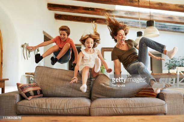 race for the best spot on the sofa. mother and children jumping. - alegria imagens e fotografias de stock
