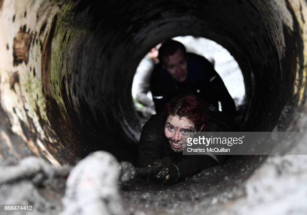 Race goer makes her way up a manhole as competitors take part in the annual McVities Mud Madness 8km cross country run on April 9, 2017 in Portadown,...