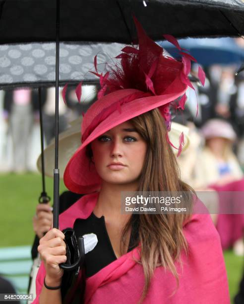 Race goer shelters from the rain under an umbrella on Ladies Day Royal Ascot.