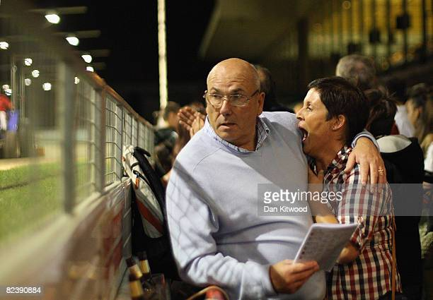 Race goers embrace whilst reading the race guide during the farewell gala evening at Walthamstow Greyhound Stadium on August 16 2008 in London...