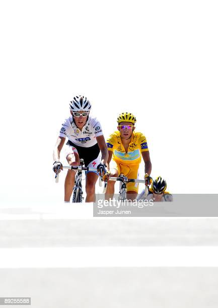Race leader Alberto Contador of Spain and team Astana crosses the finishline flanked by Andy Schleck of Luxembourg and team Saxo Bank and backdropped...