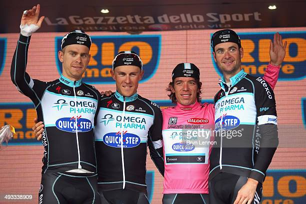 Race leader and wearer of the Maglia Rosa Rigoberto Uran of Colombia and Omega Pharma-Quickstep celebrates on the podium with team-mates Pieter Serry...
