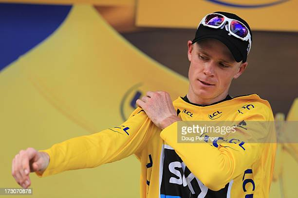 Race leader Chris Froome of Great Britain and Team Sky Procycling puts on the yellow jersey after winning stage eight of the 2013 Tour de France a...