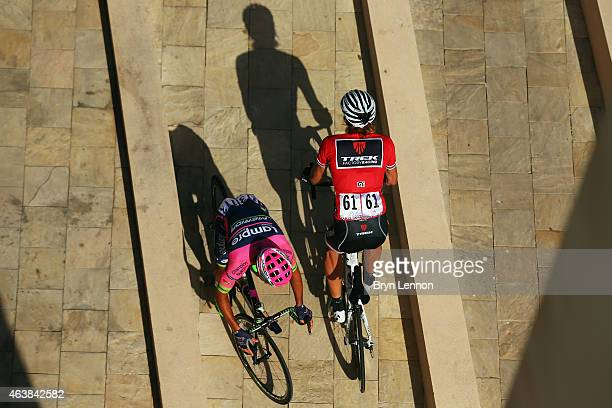Race leader Fabian Cancellara of Switzerland and Trek Factory Racing passes Roberto Ferrari of Italy and Lampre-Merida as he rides to sign in for...