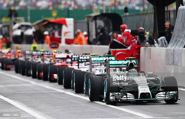Race leader Nico Rosberg of Germany and Mercedes GP and his fellow drivers are held in the pit lane prior to a restart during the Japanese Formula...
