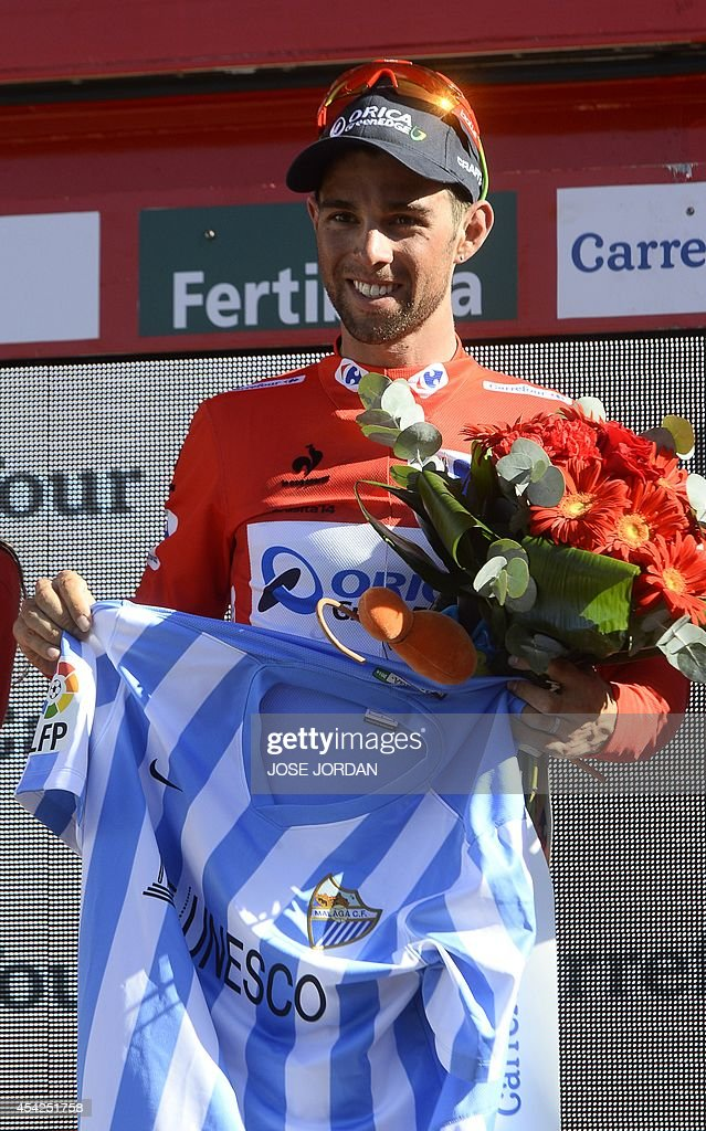 Race leader Orica GreenEdge's (OGE) Australian rider Michael Matthews holds a jersey of Malaga CF as he celebrates on the podium after the fifth stage of the 69th edition of 'La Vuelta' Tour of Spain, a 180km ride from Priego de Cordoba to Ronda, on August 27, 2014.