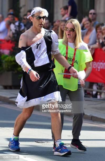 A race marshal assists a fun runner in costume along the course during the Virgin London Marathon on April 22 2018 in London England