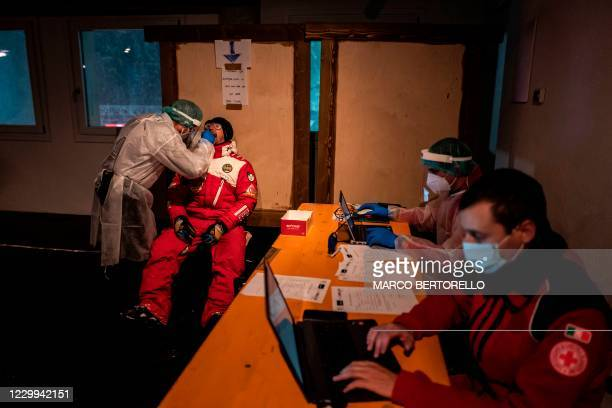 Race marshall undergoes a swab test organized by members of the Italian Red Cross , prior to receive his accreditation for the World Cup Ski Event at...