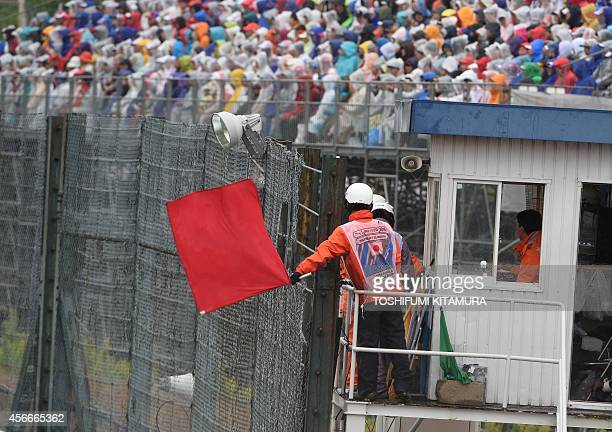 A race marshall waves a red flag to signal the race to be stopped due to heavy rain at the Formula One Japanese Grand Prix in Suzuka on October 5...