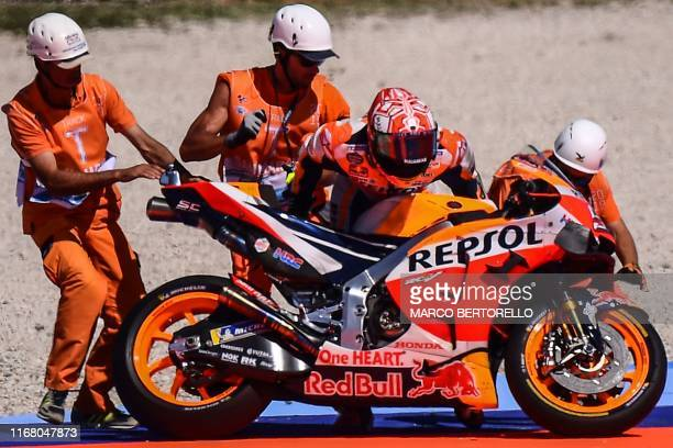 Race marshalls help Repsol Honda Team Spanish rider, Marc Marquez pick his motorbike after he fell during a free practice session ahead of the San...