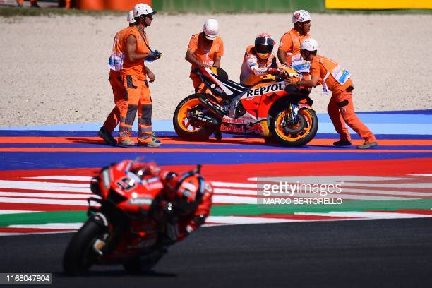 Race marshalls help Repsol Honda Team Spanish rider Marc Marquez pick his motorbike after he fell as Ducati Team Italian rider Danilo Petrucci rides...