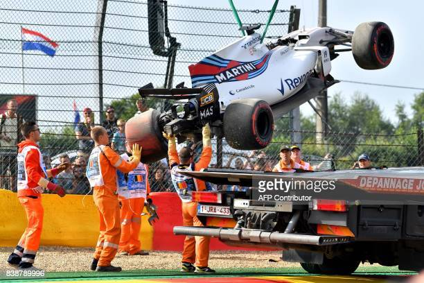 TOPSHOT Race marshalls lift Williams' Brazilian driver Felipe Massa's car after he crashed during the first practice session at the SpaFrancorchamps...