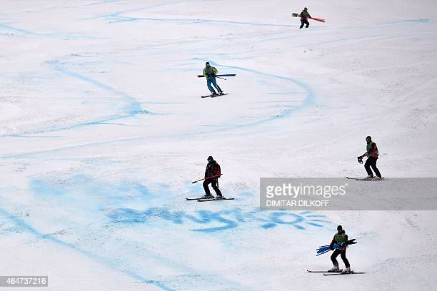 Race marshalls remove slalom gates from the slope after the Fis Alpine Ski World Cup women's Super G race was canceled due to heavy fog in Bansko on...