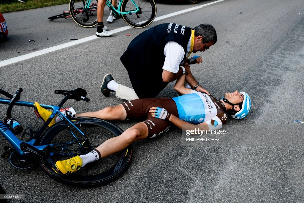 A race medic check France's Axel Domont shoulder after he was caught in a massive pack fall in the last kilometers of the fourth stage of the 105th edition of the Tour de France cycling race between La Baule and Sarzeau, western France, on July 10, 2018.
