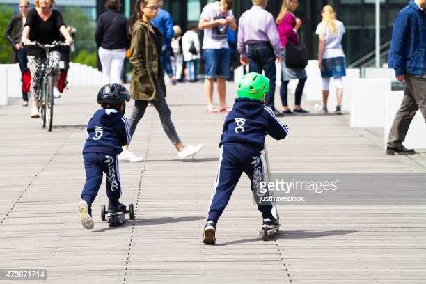 race of boys on scooters - brand name stock pictures, royalty-free photos & images