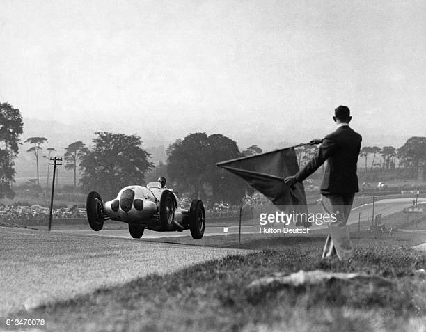 A race official waves a flag as Bernd Rosemeyer races past in his MercedesBenz racecar during the Donnington Park Grand Prix Rosemeyer eventually won...