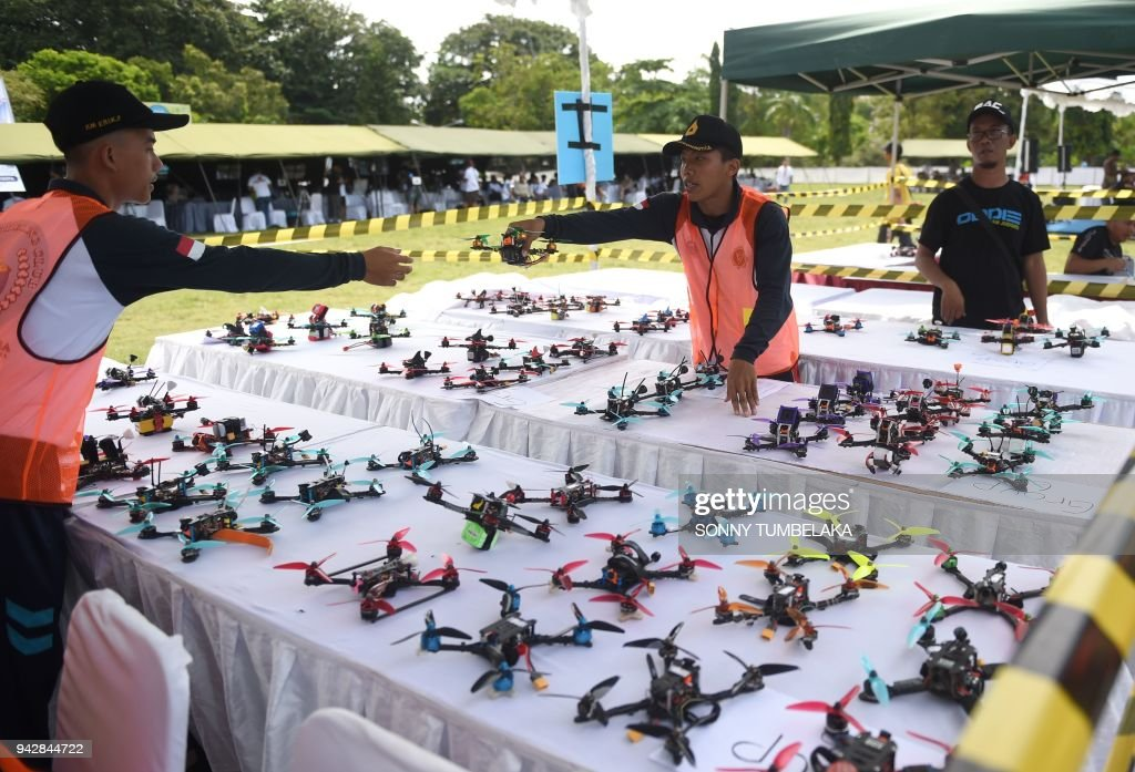 Race officials prepare drones prior to the FAI Drone Racing World Cup event in Denpasar on Indonesia's resort island of Bali on April 7, 2018. /