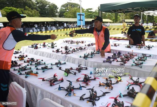 Race officials prepare drones prior to the FAI Drone Racing World Cup event in Denpasar on Indonesia's resort island of Bali on April 7 2018 / AFP...