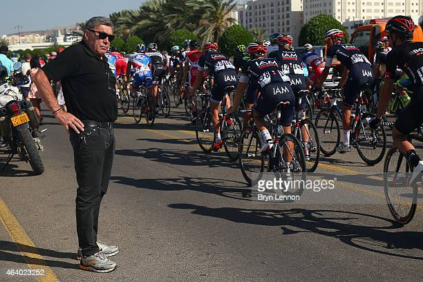 Race Organiser Eddy Merckx watches the peloton ride slowly across the finish line after the stage was cancelled due to safety concerns on stage 5 of...