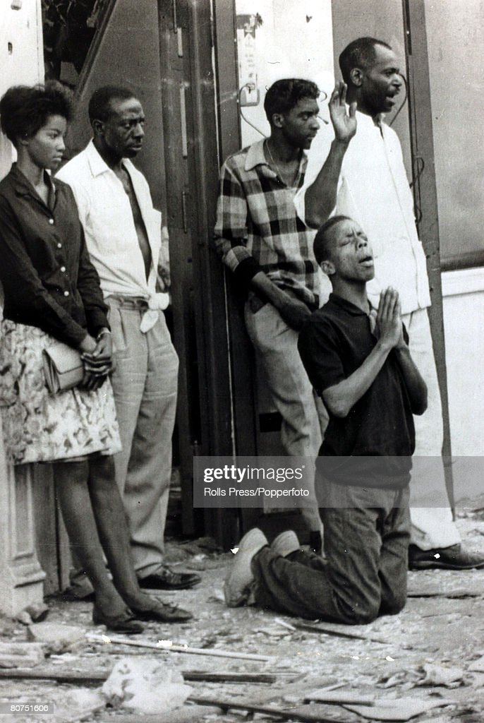 16th September 1963, Birmingham, Alabama, A black youth kneels in prayer, alongside other solemn people, after a baptist church had been bombed leaving 4 children dead in the blast