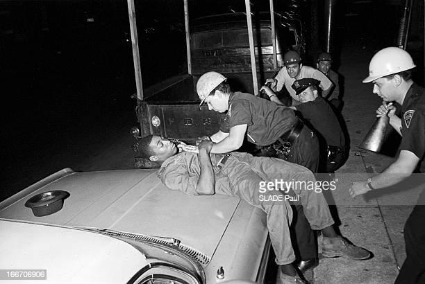 Race Riots At Newark, New Jersey. New Jersey, Newark- 17 Juillet 1967- Graves emeutes raciales près de New York: la nuit, un jeune homme Afro-américain allongé sur le capot avant d'une voiture stationné, son chapeau retourné derrière lui, fouillé par un groupe d'hommes de la Police nationale, l'un d'eux tenant une lampe torche, d'autres en embuscade derrière un véhicule stationné.