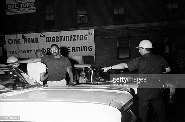 Race Riots At Newark New Jersey New Jersey Newark 17 Juillet 1967 Graves emeutes raciales près de New York la nuit fouille d'un homme Afroaméricain...