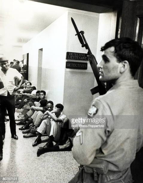 27th July 1967 Detroit Michigan An armed Michigan National Guardsman stands guard over black suspects arrested after 4 days of violent racial warfare...