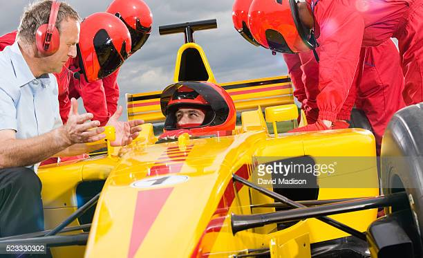 Race Team Leader Discussing Strategy With Racecar Driver