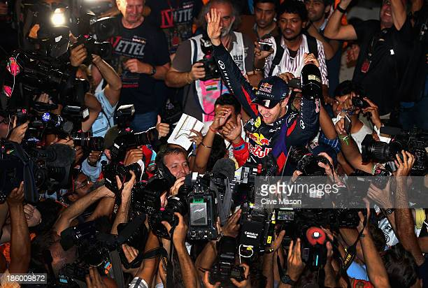 Race winner and 2013 Formula One World Champion Sebastian Vettel of Germany and Infiniti Red Bull Racing celebrates with team mates in the pitlane...