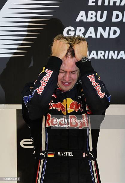 Race winner and F1 2010 World Champion Sebastian Vettel of Germany and Red Bull Racing celebrates on the podium following the Abu Dhabi Formula One...