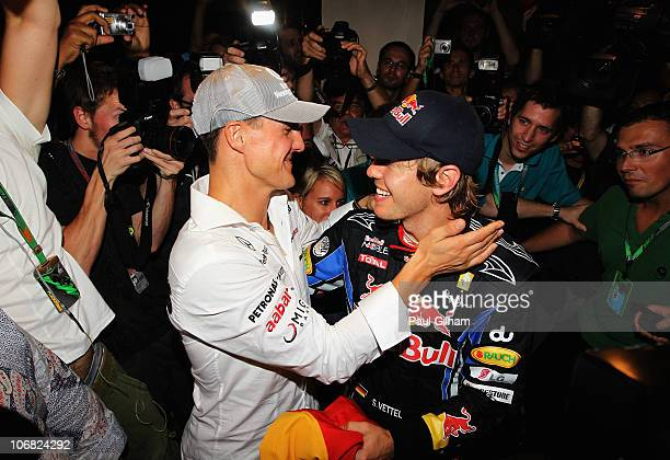 Race winner and F1 2010 World Champion Sebastian Vettel of Germany and Red Bull Racing is congratulated by Michael Schumacher of Germany and Mercedes...