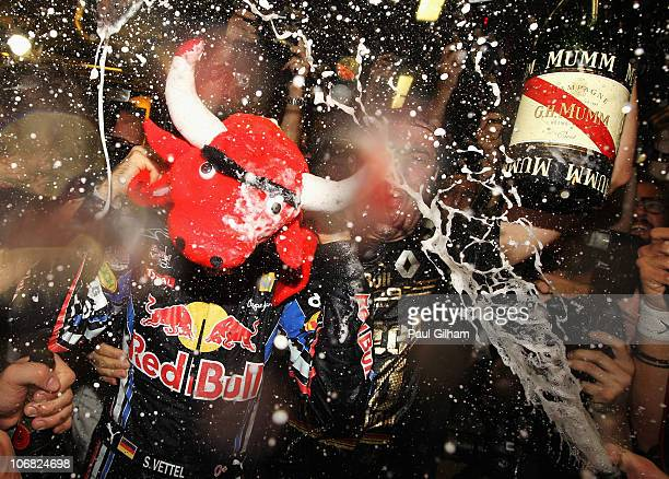 Race winner and F1 2010 World Champion Sebastian Vettel of Germany and Red Bull Racing celebrates with team mates in their team garage following the...