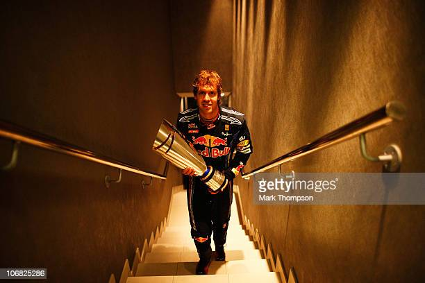 Race winner and F1 2010 World Champion Sebastian Vettel of Germany and Red Bull Racing carries his winners trophy back to his changing room following...
