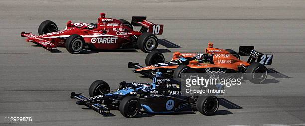 Race winner and points champion Dario Franchitti in car 27 splits between Dan Wheldon in car 10 and Danica Patrick late in the race Sunday September...