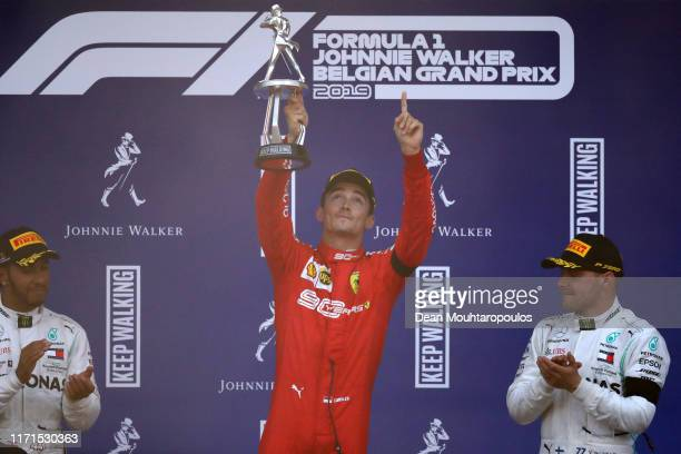 Race winner Charles Leclerc of Monaco and Ferrari celebrates on the podium with second placed Lewis Hamilton of Great Britain and Mercedes GP and...