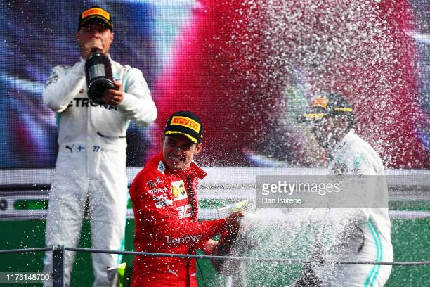 Race winner Charles Leclerc of Monaco and Ferrari celebrates on the podium with second placed Valtteri Bottas of Finland and Mercedes GP and third...