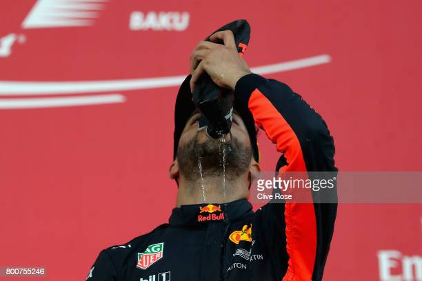 Race winner Daniel Ricciardo of Australia and Red Bull Racing celebrates his win on the podium with a shoey during the Azerbaijan Formula One Grand...