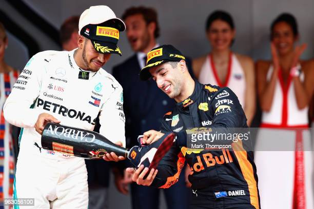 Race winner Daniel Ricciardo of Australia and Red Bull Racing celebrates on the podium with a shoey poured by Lewis Hamilton of Great Britain and...